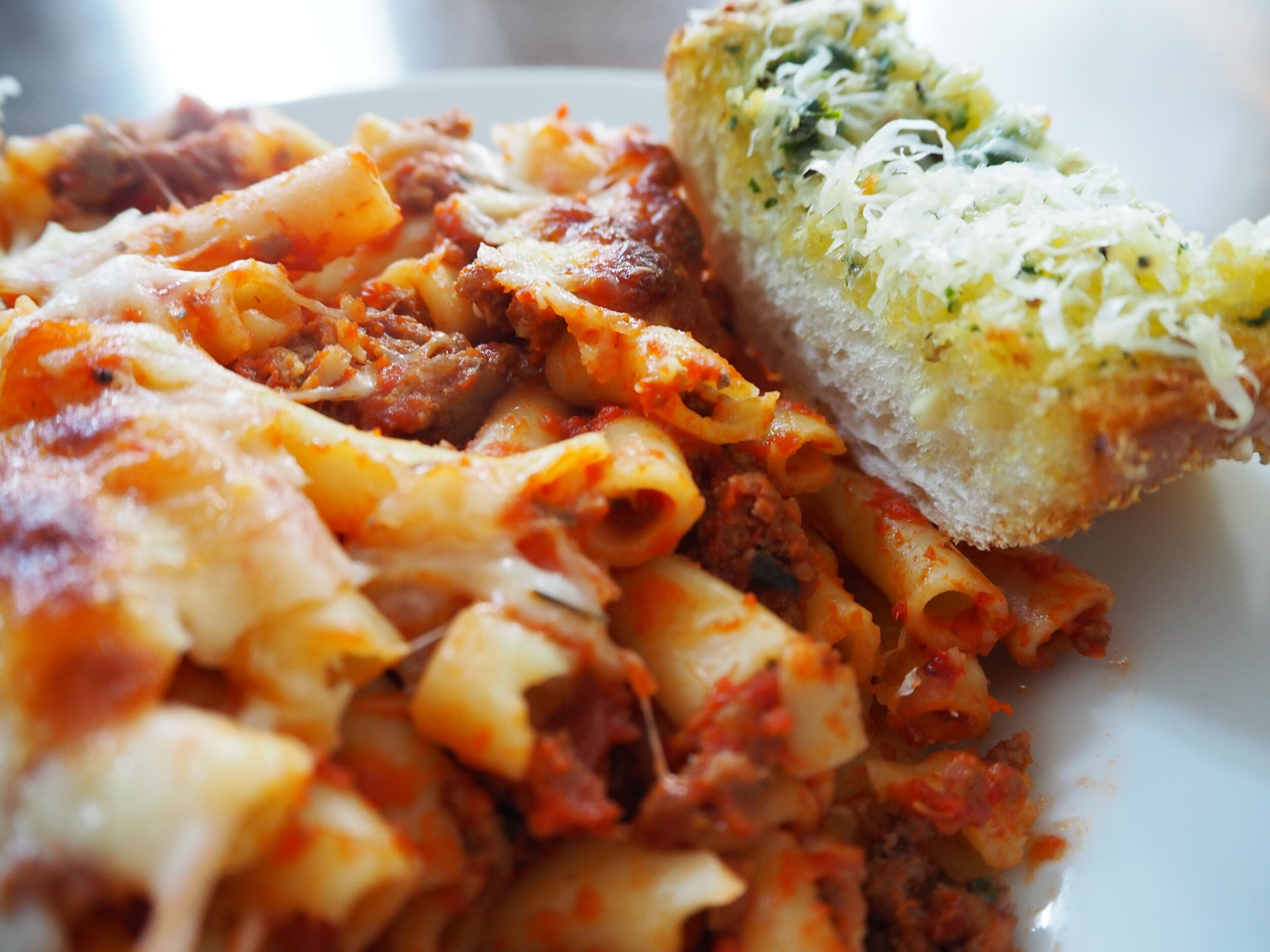 pasta with red sauce and slice of bread